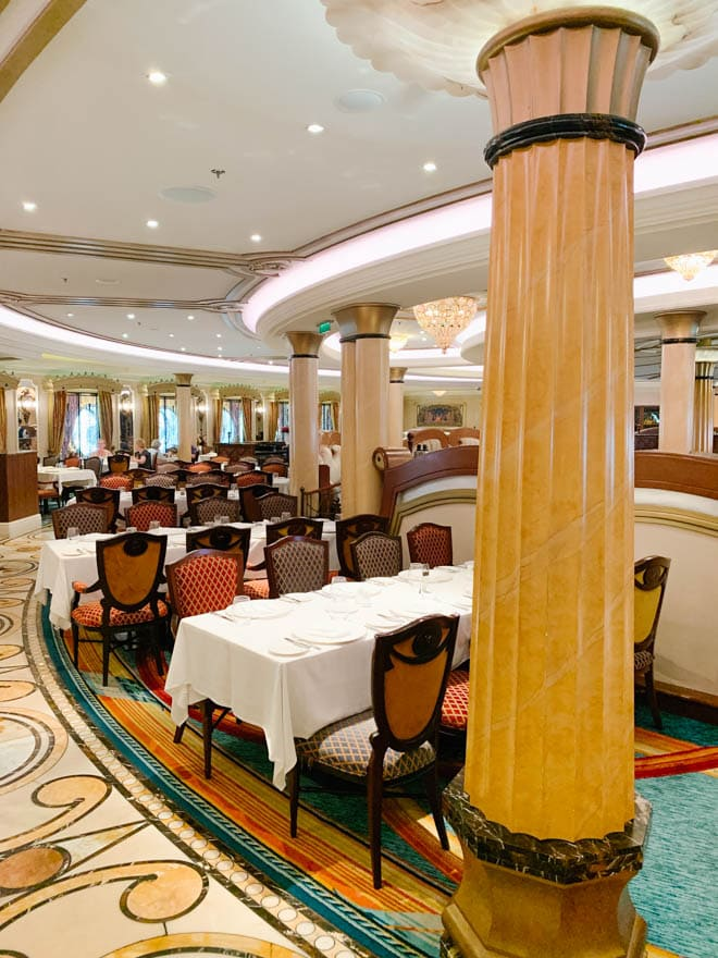 The Royal Palace dining room on Disney Dream with tables and chairs.