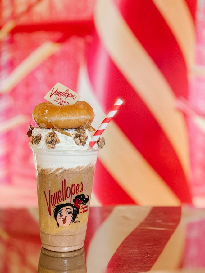 Peanut butter milkshake with whipped cream and a donut in front of a red background.