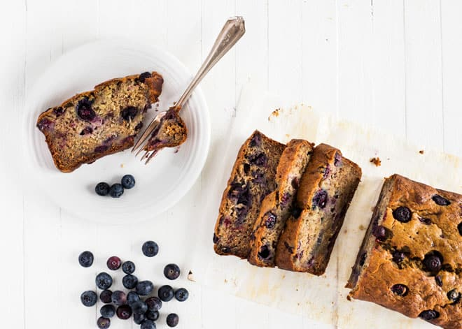 Three slices of banana bread and a handful of blueberries on a white background