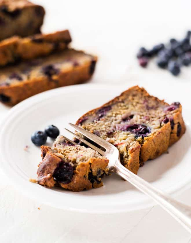 a fork cutting into a slice of blueberry banana bread