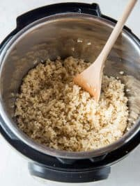 An open instant pot with cooked brown rice and a wooden spoon.