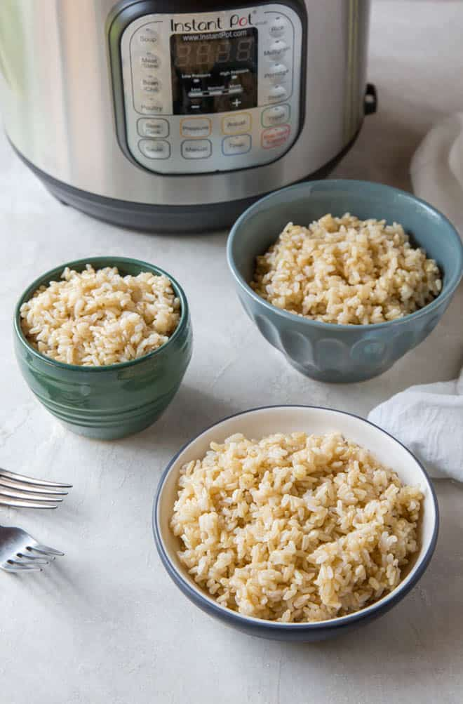 Three bowls filled with brown rice sitting in front of an instant pot.