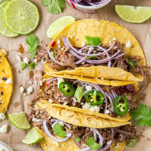 Three slow cooker barbacoa tacos on a table with assorted toppings on the side.
