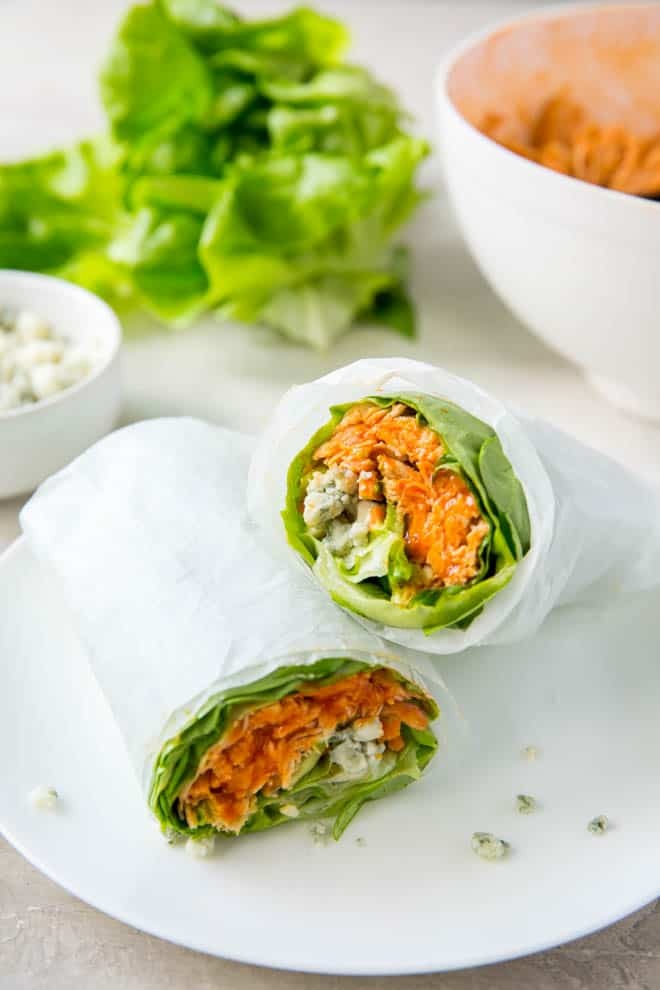 Two buffalo chicken lettuce wraps sitting on top of each other with white wrapping.