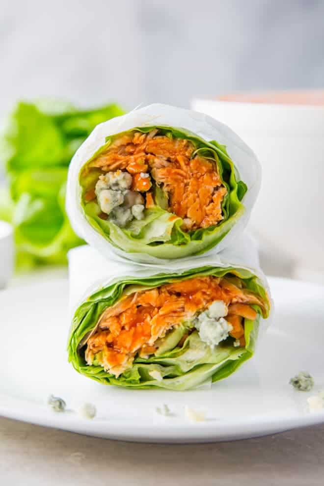 Two buffalo lettuce chicken wraps stacked on top of each other on a white background.
