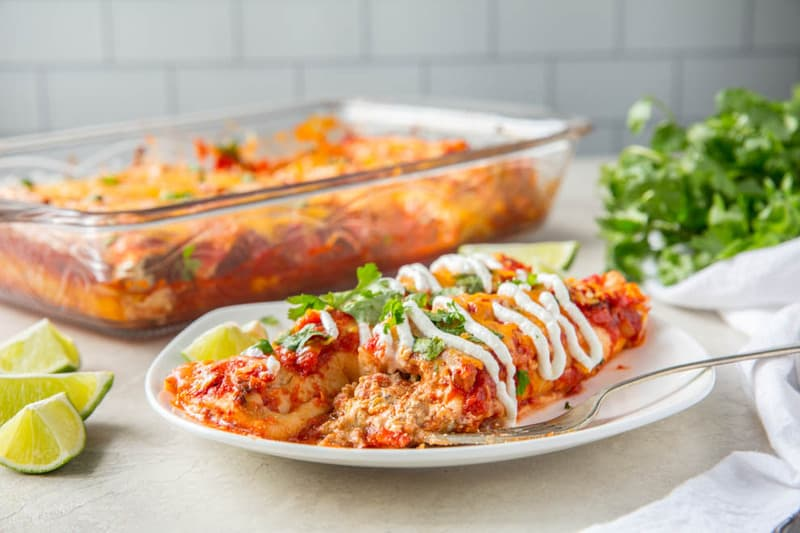 Two turkey enchiladas sitting on a white plate in front of a casserole dish full of enchiladas.