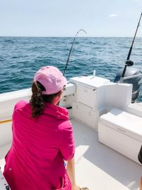 Deep sea fishing over the side of a boat.