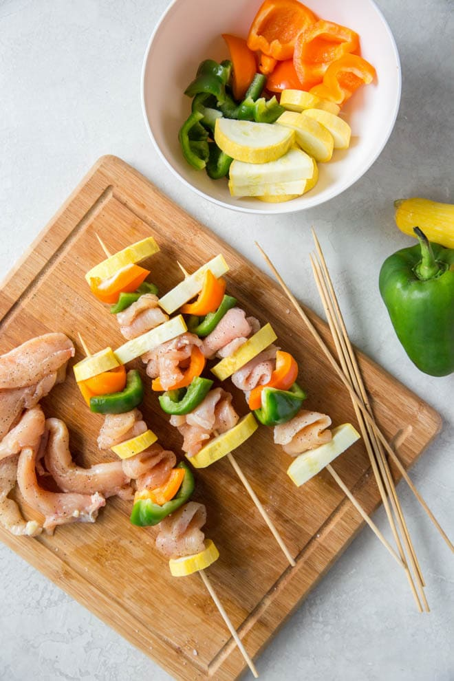 Chicken kebabs sit on skewers on a wood cutting board before grilling.