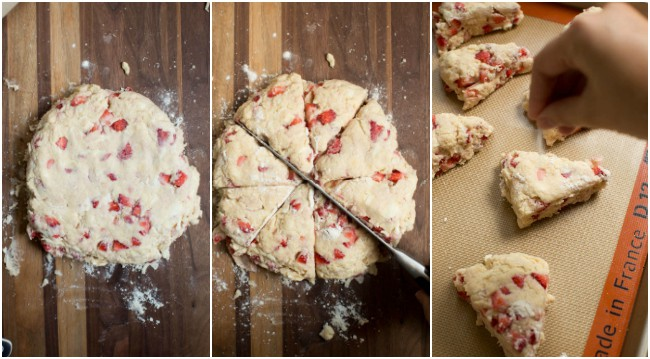 Round Strawberry scone dough on a wood backdrop with a knife cutting into scones.