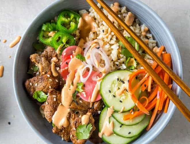 A bowl filled with brown rice, pork tenderloin, pickled veggies and sriracha mayo.