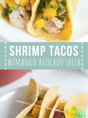 Two shrimp tacos with mango avocado salsa on a white plate.