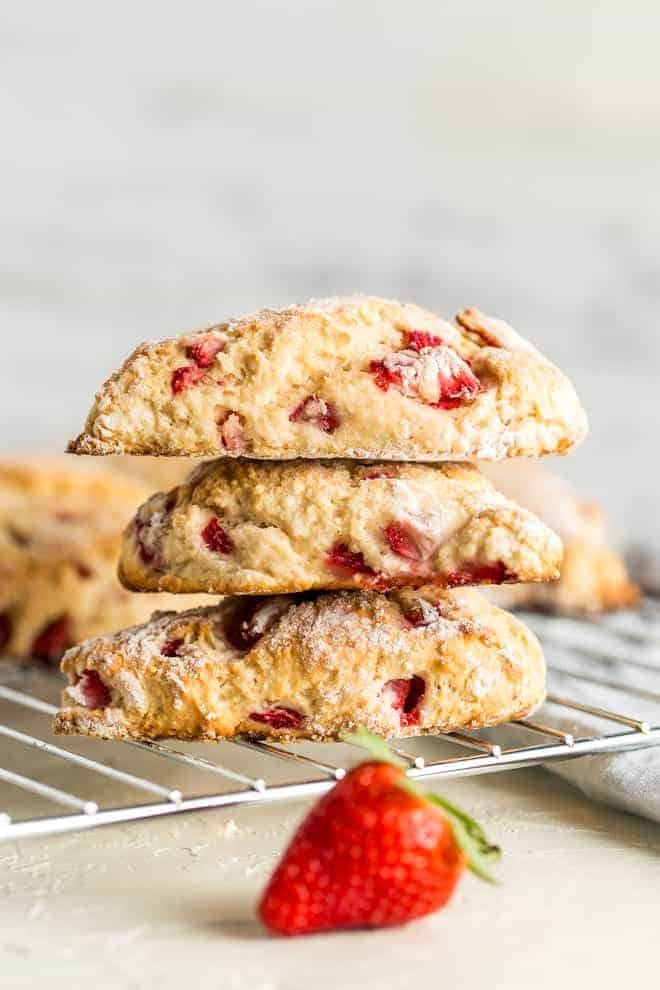 A pile of three strawberry scones sitting on a cooling rack.