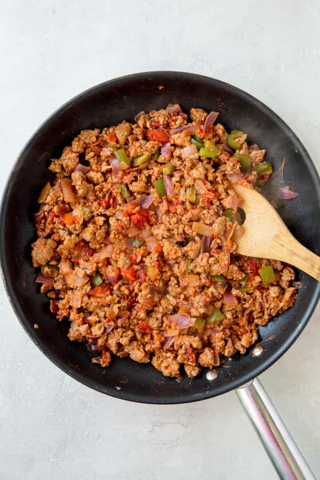 Ground turkey with spices and other seasonings cooked in a small nonstick pan.