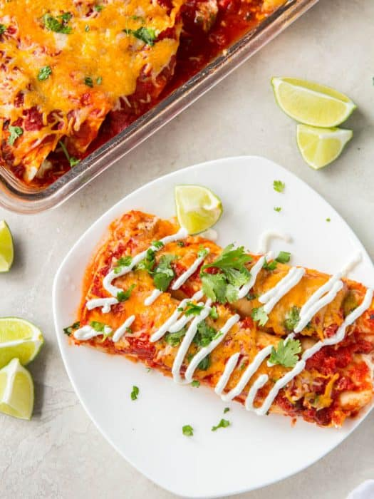 Two turkey enchiladas sit on a white plate with a casserole dish full of enchiladas off to the side.