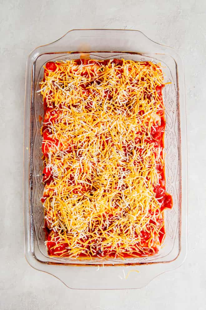 Cheese and sauce on top of enchiladas sitting in a casserole dish.