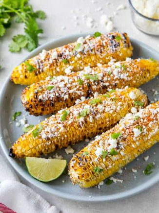 Four pieces of Mexican street corn sitting on a blue plate.