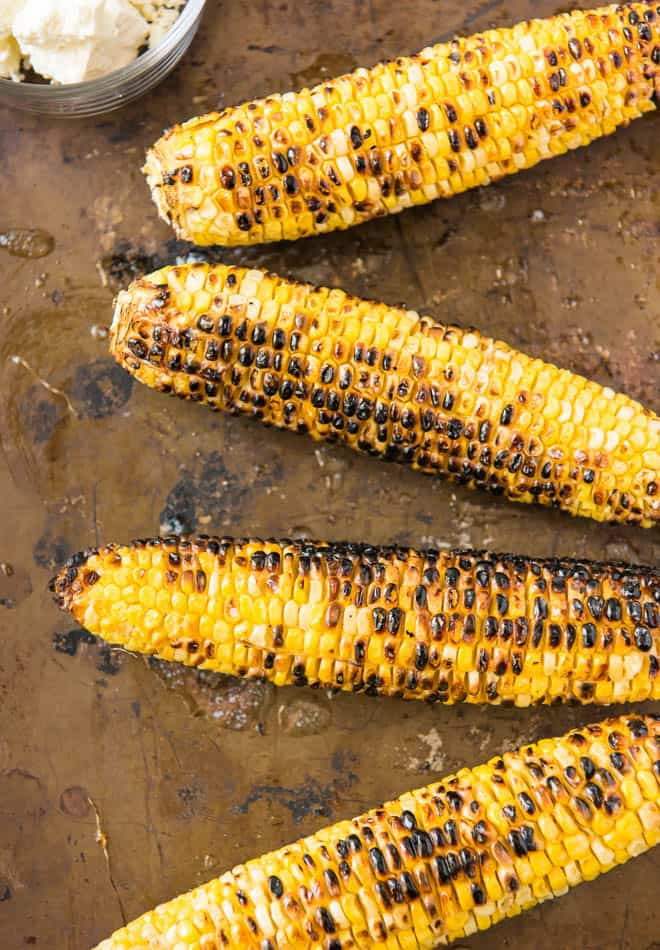 Four pieces of grilled corn.