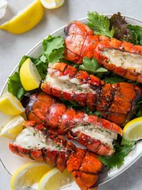 Four grilled lobster tails sitting on a plate with lemon wedges.