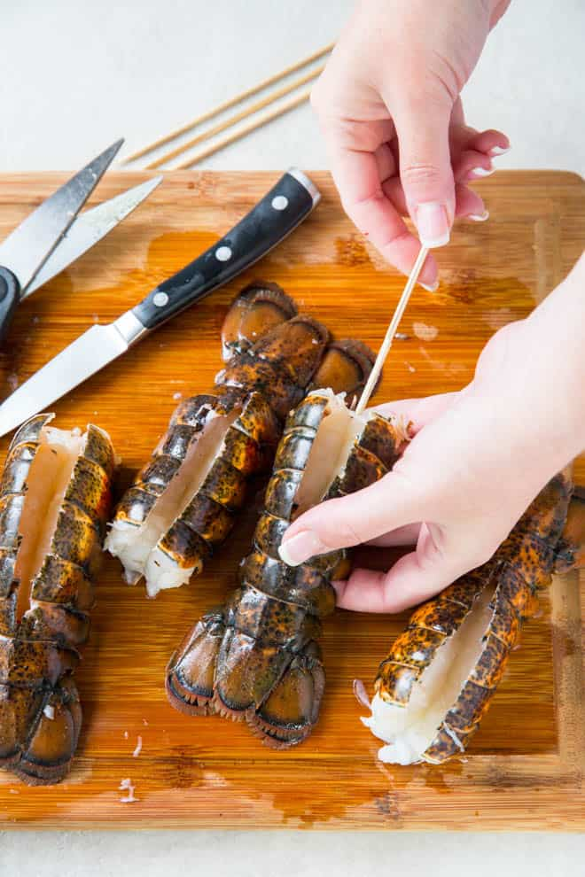 Put a skewer in the lobster tails to prevent tails from curling while grilling.