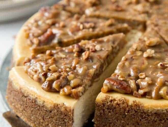 A cake knife removes a piece of pecan pie cheesecake.
