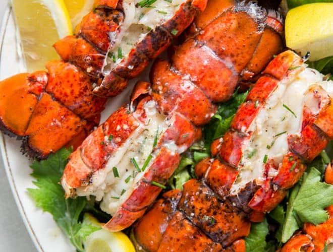 Close up of four grilled lobster tails on a plate with lemon wedges.