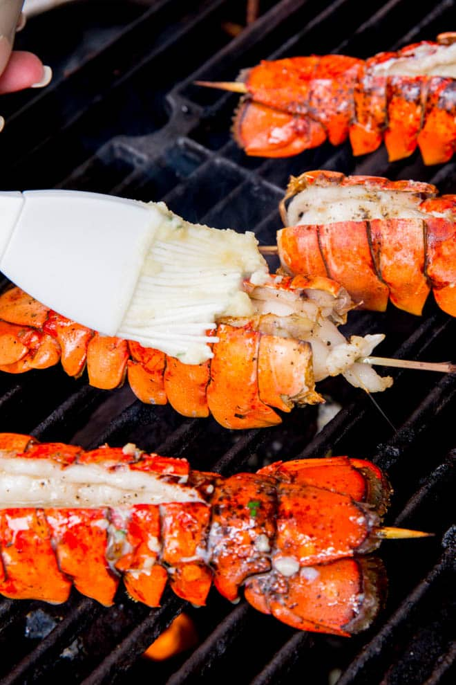 Spread garlic butter over the grilled lobster tails.
