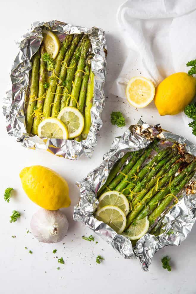 Two packets of grilled asparagus with lemon slices and lemon zest.