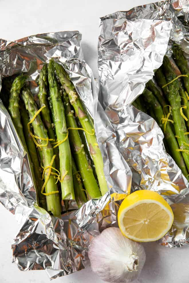 Asparagus with lemon slices and lemon zest in foil.