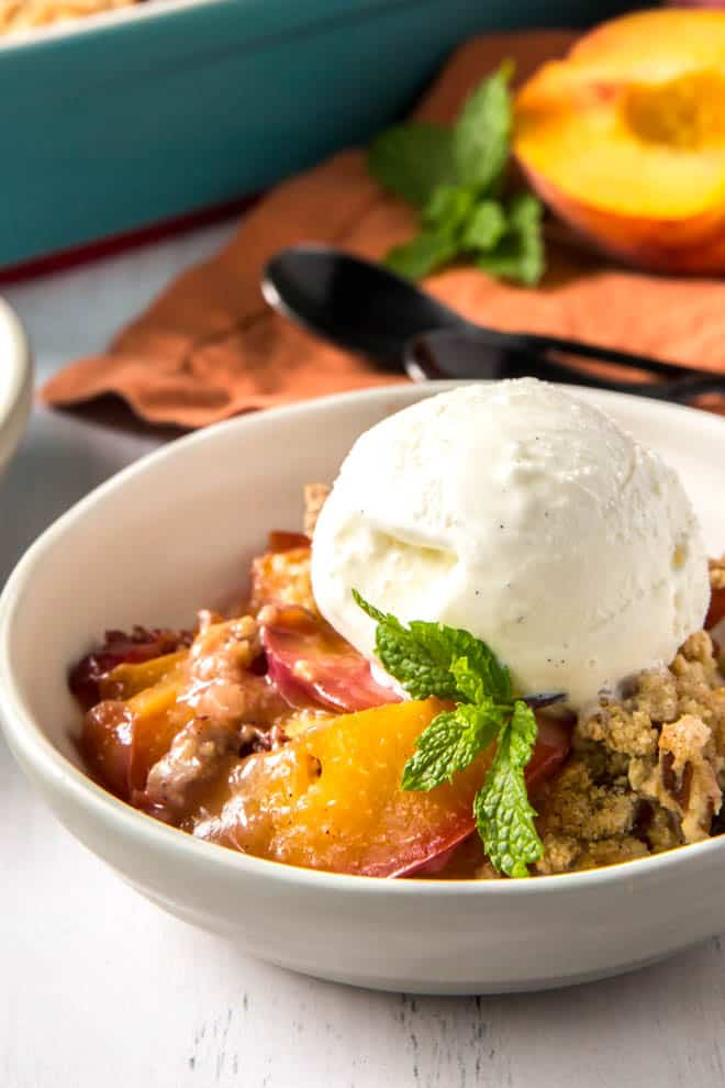 A bowl of peach cobbler with a scoop of ice cream.