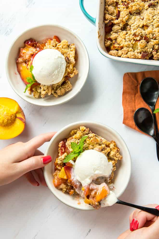 Two bowls of peach cobbler with scoops of vanilla ice cream.