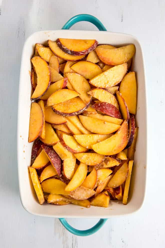 Fresh peaches in the bottom of a white rectangle casserole dish