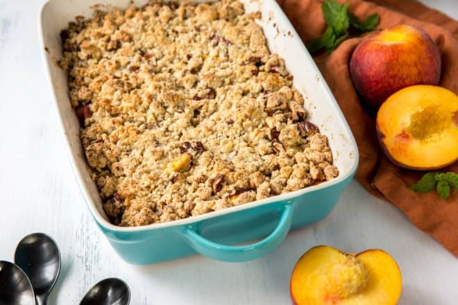 Baked peach crumble in a rectangle casserole dish.