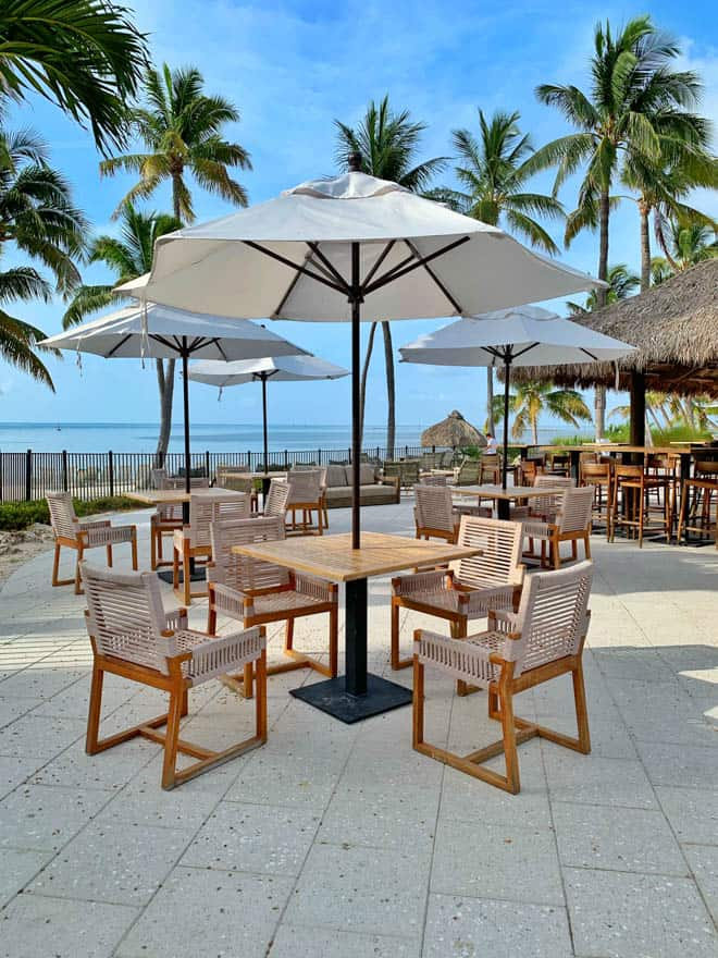 Tables and chairs on the patio of the Tiki Bar at Amara Cay