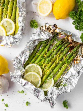 Grilled asparagus in foil with lemon slices and lemon zest.