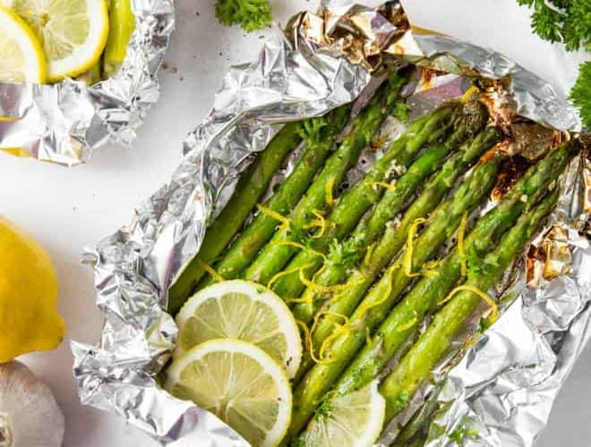 Grilled asparagus in foil with lemon slices and lemon zest.