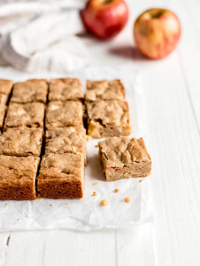 Apple blondies on parchment paper with apples in background