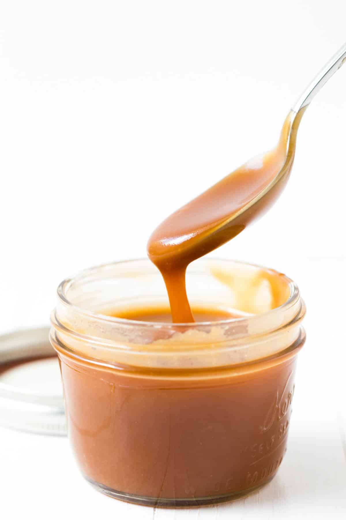 caramel sauce dripping off a spoon into a glass of caramel