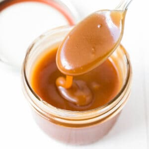a jar of homemade caramel sauce with a spoon of sauce