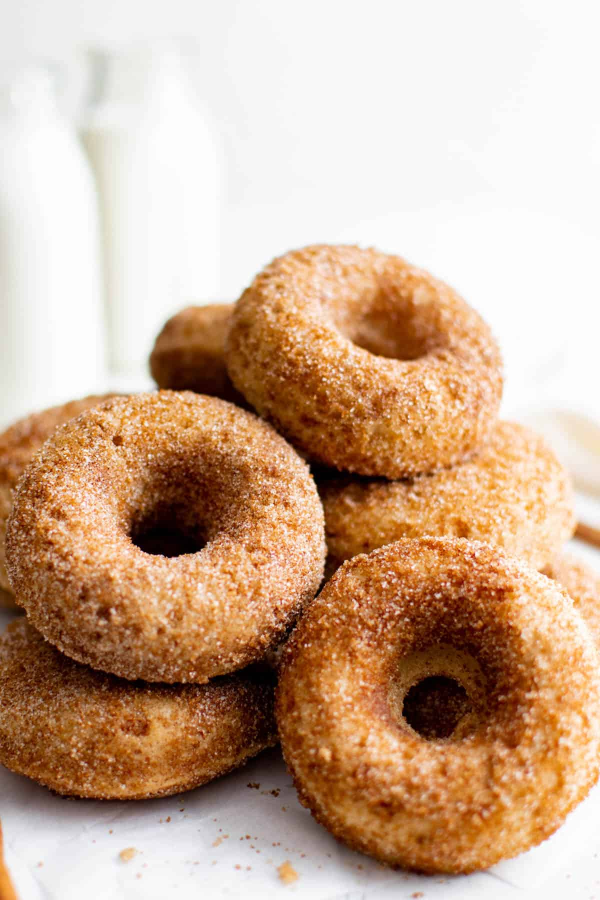 a pile of apple cider donuts next to a glass milk jug