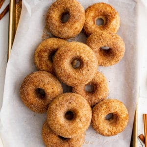 a pile of apple cider donuts on a piece of parchment paper on a baking sheet
