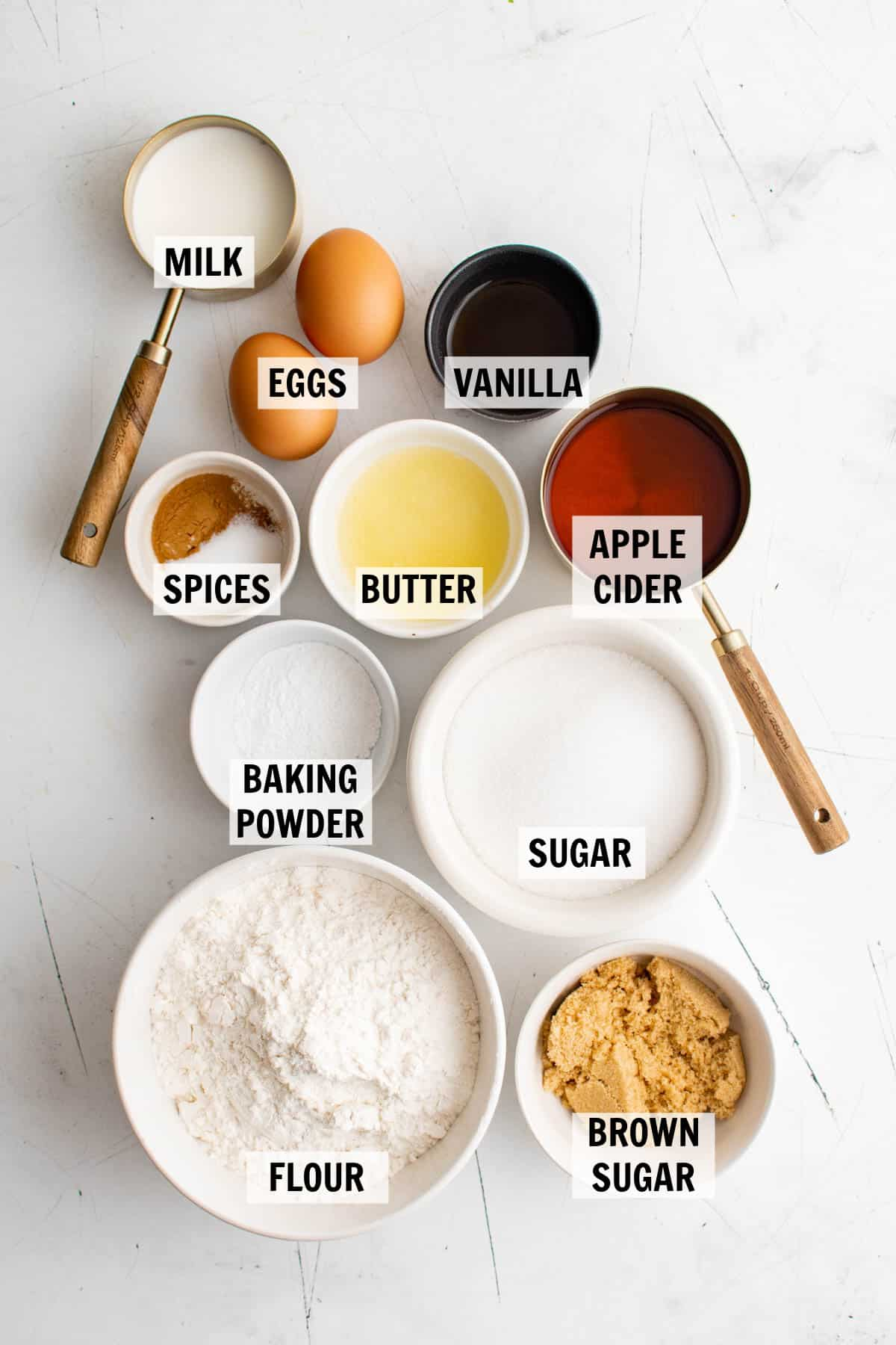 all of the ingredients for baked apple cider donuts in bowls on a white tabletop