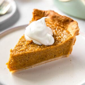 one slice of sweet potato pie on a plate with a scoop of whipped cream on top