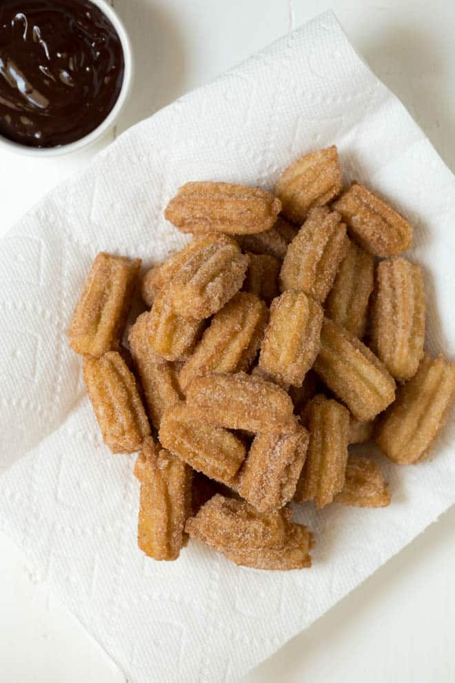 large plate of churros with chocolate dipping sauce on the side