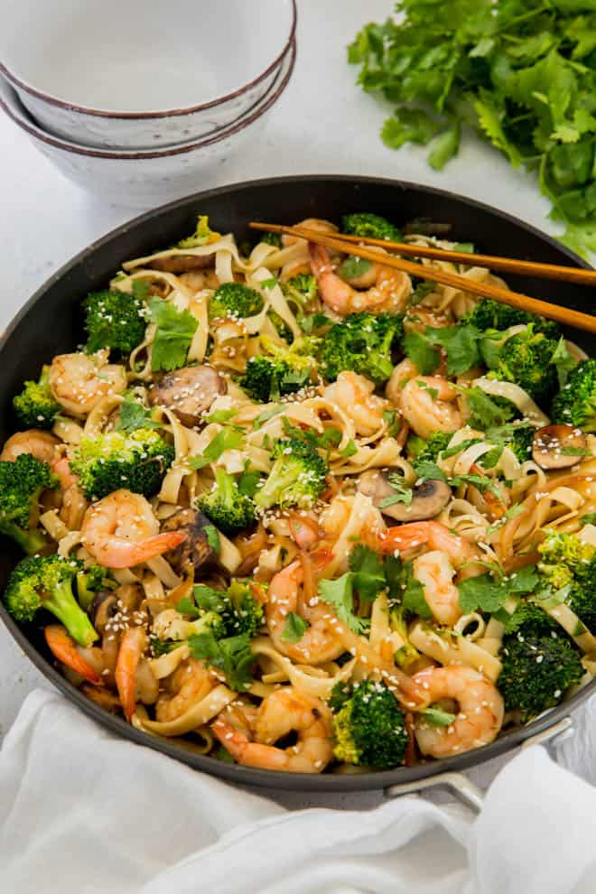noodles, shrimp, broccoli and mushrooms cooked in a skillet