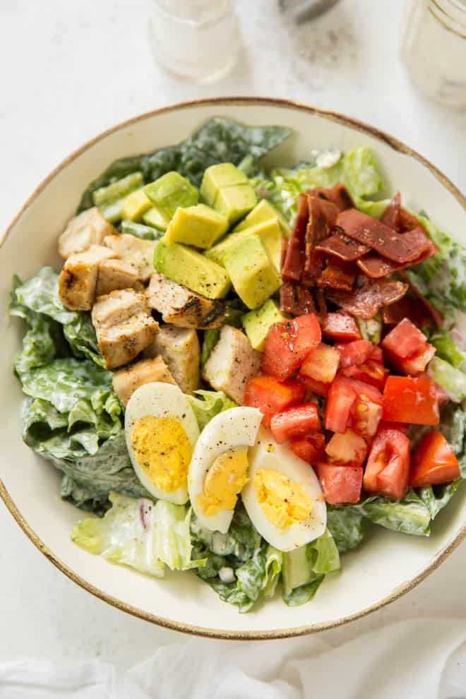 small white bowl with lettuce, boiled egg, tomatoes, turkey and avocado layered on top