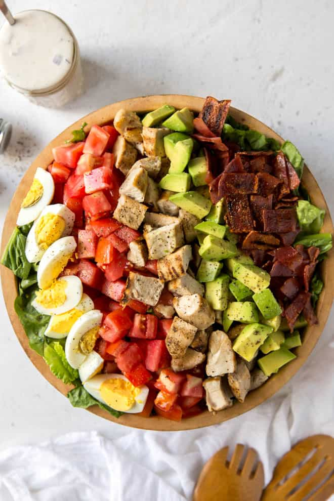 a large bowl sitting on a table filled with cobb salad ingredients