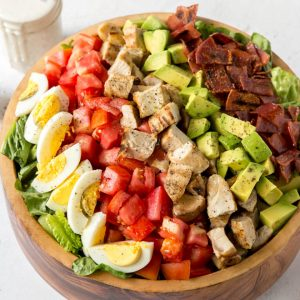 a large wooden bowl with lettuce, boiled egg, tomatoes, grilled turkey, avocado and turkey bacon