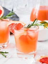 One clear glass with grapefruit gin fizz drink, ice cubes and a sprig of fresh rosemary sitting on a white table