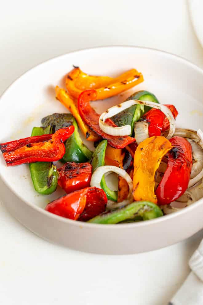 grilled peppers and onions in a white bowl on a white table