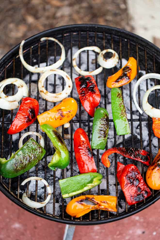 sliced bell peppers and onions on a grill grate